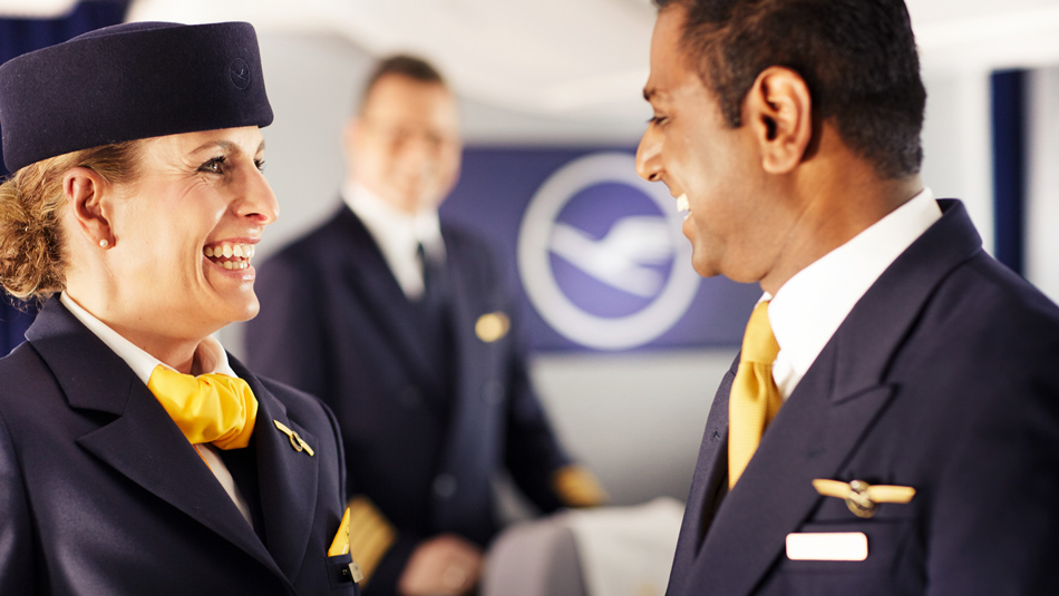 Laughing cabin crew members standing in an airplane and talking