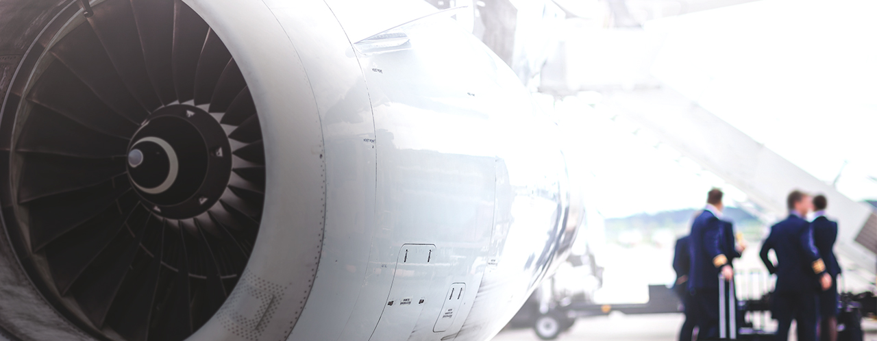 Aircraft turbine in the foreground, an aircraft crew next to the gangway in the background