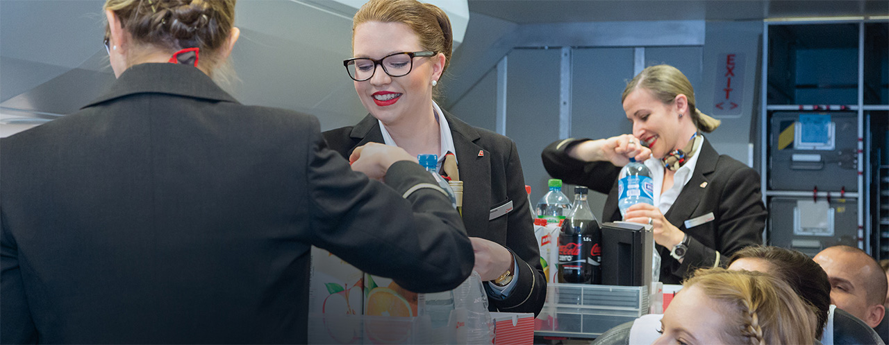 Three members of the cabin crew serve passengers drinks