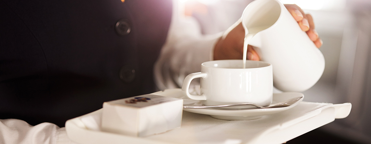 Close-up of a tray in the hands of a flight attendant pouring milk into a cup of coffee