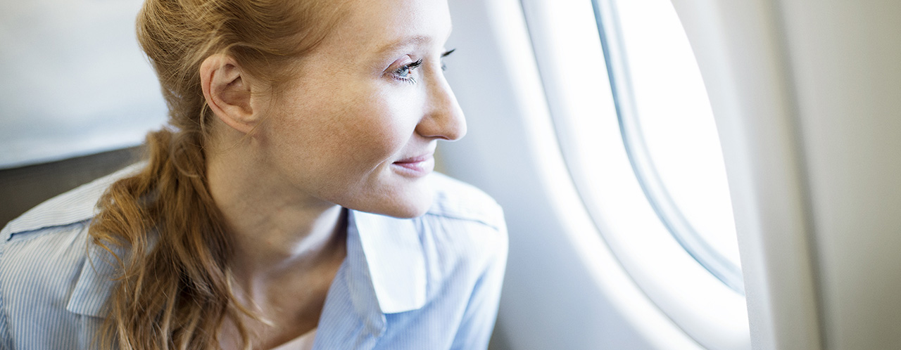 A passenger looks out the window of an airplane