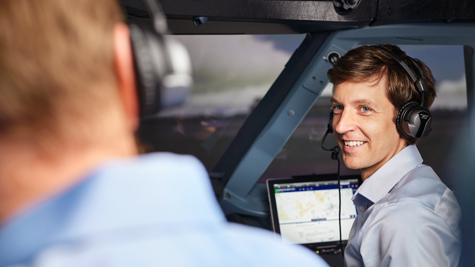 A man wearing headphones sits in an aircraft cockpit and smilingly looks at his colleague