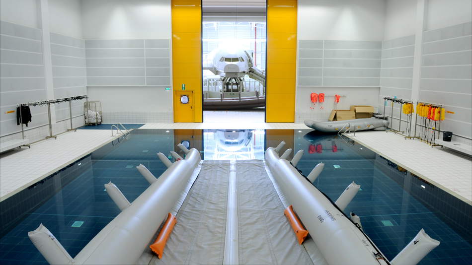In a training hall, a rescue chute runs into a water basin