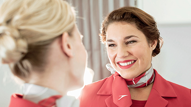 Two smiling flight attendants of Austrian Airlines wear uniforms and scarves