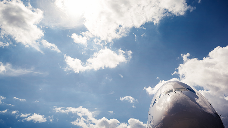 The nose of an airplane with Lufthansa logo from below in front of a blue sky with some clouds