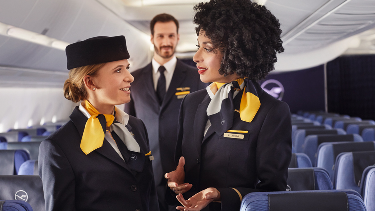 Two female and one male flight attendant on board an empty Lufthansa aircraft