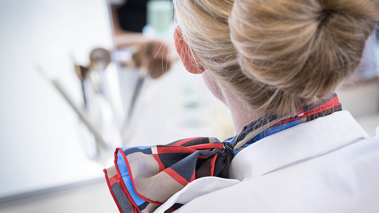 Close-up of a SWISS flight attendant with her hair pinned up and silk scarf from behind