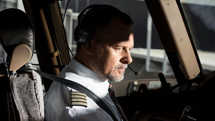 An elderly pilot with a full beard looks intently at  Instruments in an aircraft cockpit