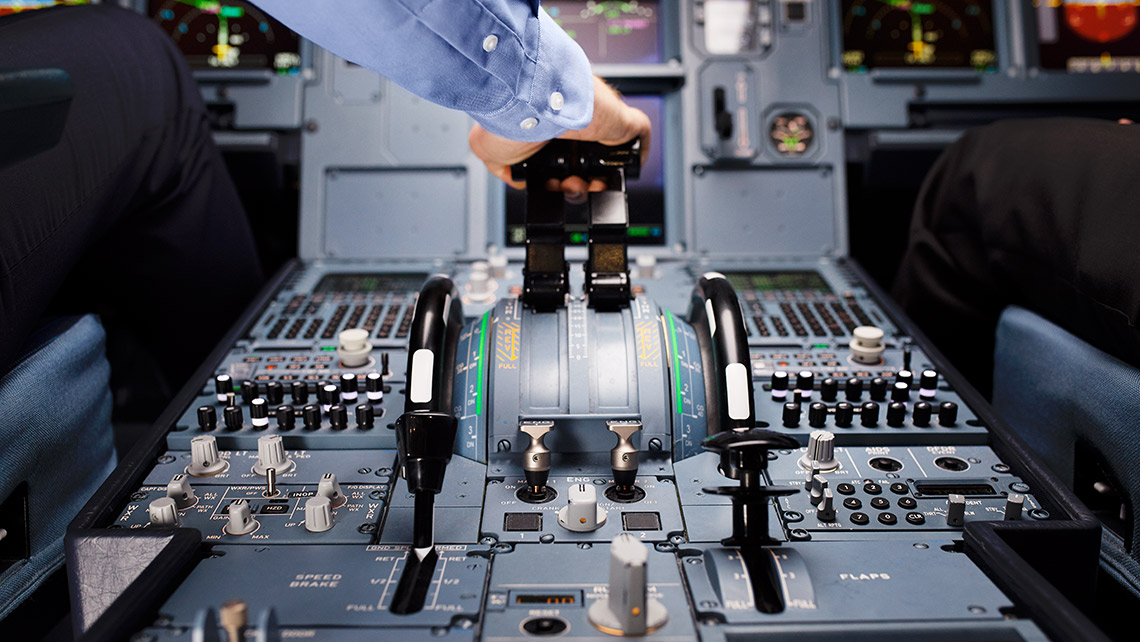 A pilot operates the thrust levers in an aircraft cockpit